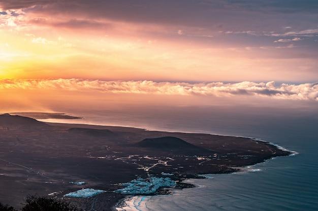 Toma aérea de una hermosa costa costera de la ciudad con nubes increíbles y luz solar a la izquierda