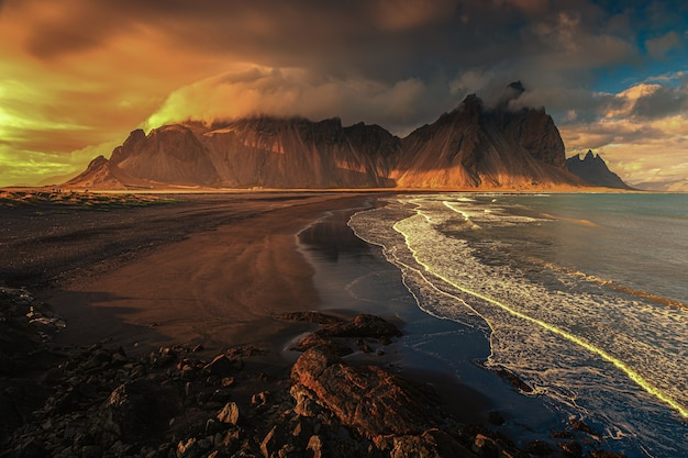 Toma aérea hermosa de una orilla del mar con colinas en el fondo al atardecer