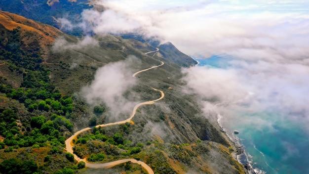 Toma aérea de hermosas colinas verdes y una carretera con curvas que bordean el increíble mar