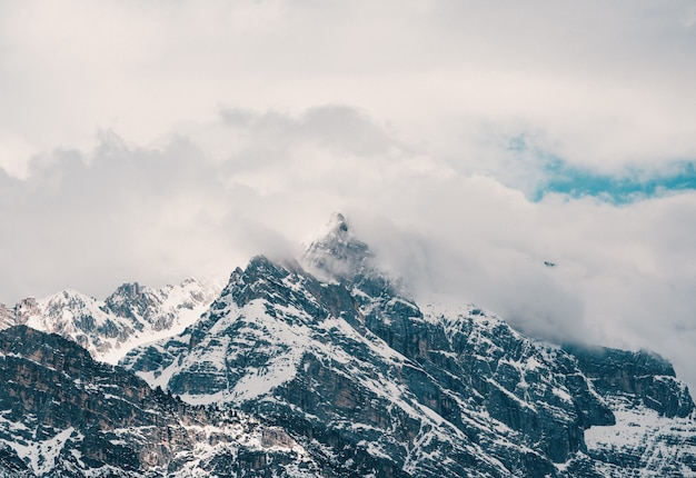 Toma aérea de hermosas montañas nevadas rocosas cubiertas de nubes