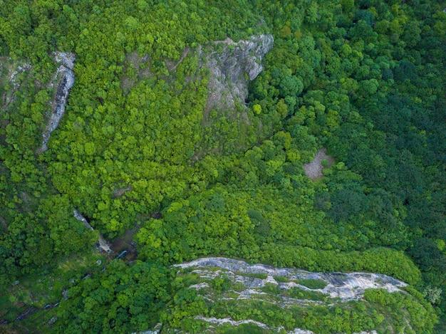Toma aérea de las hermosas montañas y valles cubiertos de césped y árboles