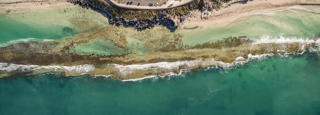 Toma aérea de las hermosas olas del mar que se encuentran con la playa