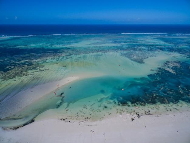 Toma aérea del hermoso océano azul tranquilo bajo el cielo azul capturado en zanzíbar, áfrica