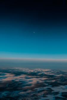 Toma aérea de un hermoso paisaje cubierto de nieve temprano en la mañana