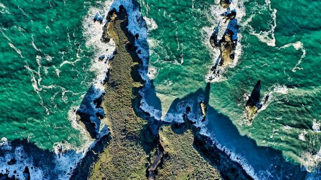 Toma aérea de hermosos arrecifes de coral y la increíble textura del agua en el océano.
