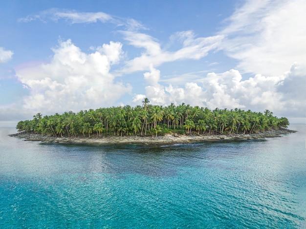 Toma aérea de una isla verde rodeada de agua clara con nubes en el