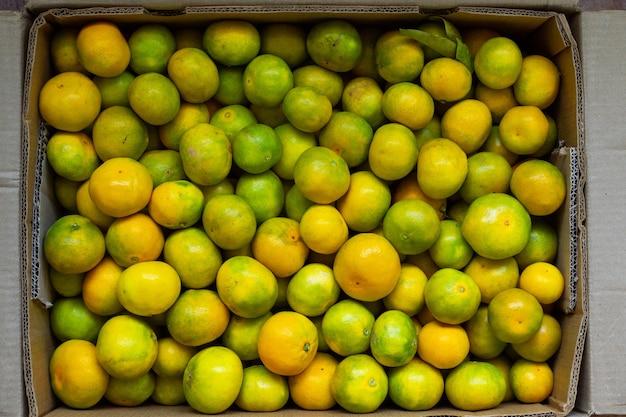 Toma aérea de una mandarina fresca dentro de la caja