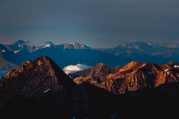 Toma aérea de montañas con un cielo azul oscuro