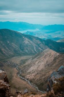 Toma aérea de montañas y río que fluye en la patagonia, argentina