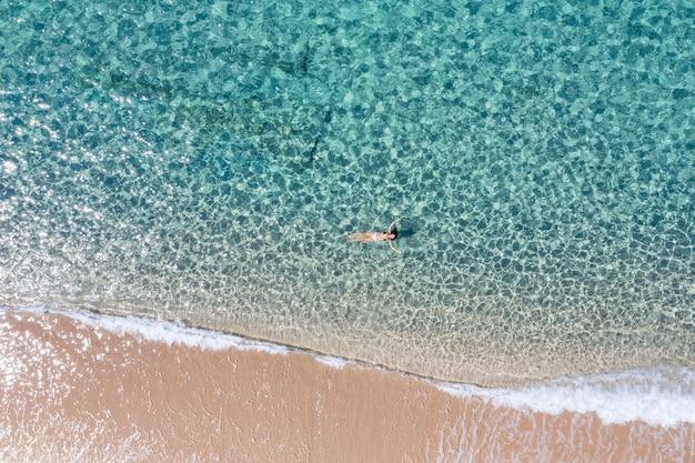 Toma aérea de una niña nadando en un mar increíble