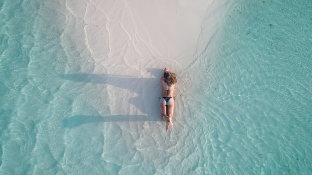 Toma aérea de una niña tendida en la arena y broncearse en la playa