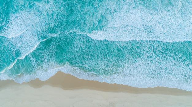 Toma aérea de olas rompiendo en la orilla. colorida playa de verano.
