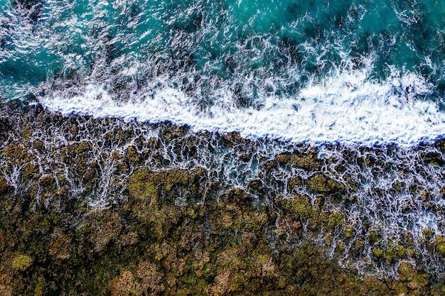 Toma aérea de una orilla rocosa con olas espumosas