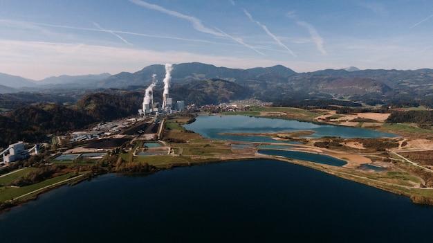 Toma aérea de un paisaje rodeado de montañas y lagos con desastre industrial
