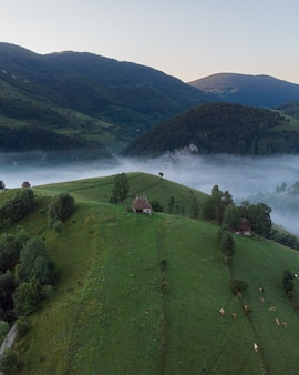 Toma aérea de una pequeña casa en un increíble paisaje de montaña en transilvania, rumania