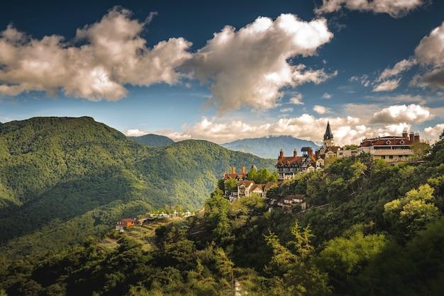 Toma aérea de un pequeño pueblo en la colina rodeado de montañas boscosas