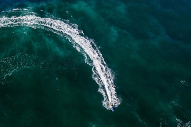 Toma aérea de una persona en moto acuática en agua de mar verde brillante