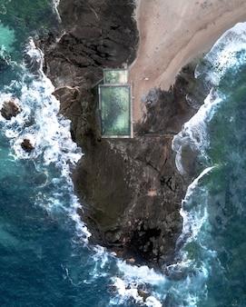 Toma aérea de personas nadando en una gran piscina construida en la costa rocosa de tailandia