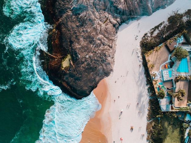 Toma aérea de una playa en río de janeiro con casas en la montaña