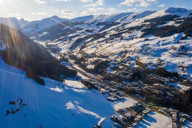 Toma aérea de un resort de snowboard en la nieve bajo la luz del sol