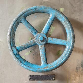 Toma aérea de una rueda antigua azul sobre un piso de concreto durante el día
