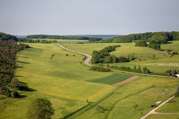 Toma aérea de tierras de cultivo bajo el cielo despejado en la región de eifel, alemania