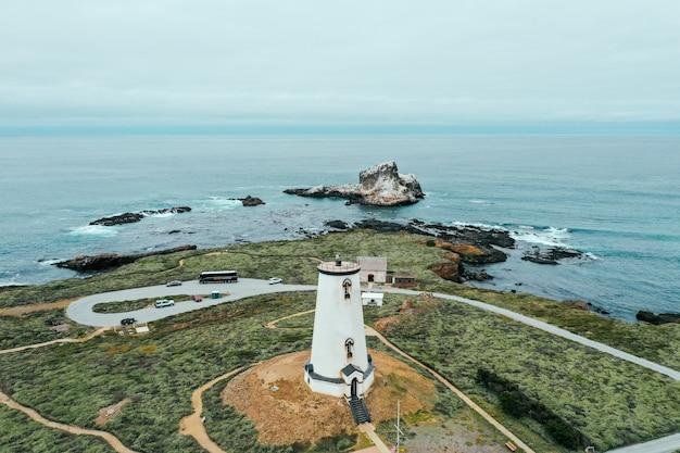 Toma aérea de una torre redonda blanca en la costa rocosa del mar