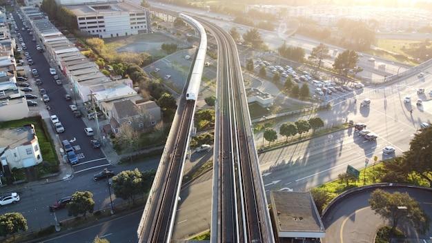 Toma aérea del tránsito rápido del área de la bahía de san francisco, el tren se acerca a la estación de daly city,