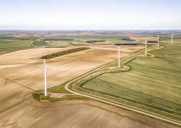 Toma aérea de las turbinas en los hermosos campos verdes cerca de las granjas aradas
