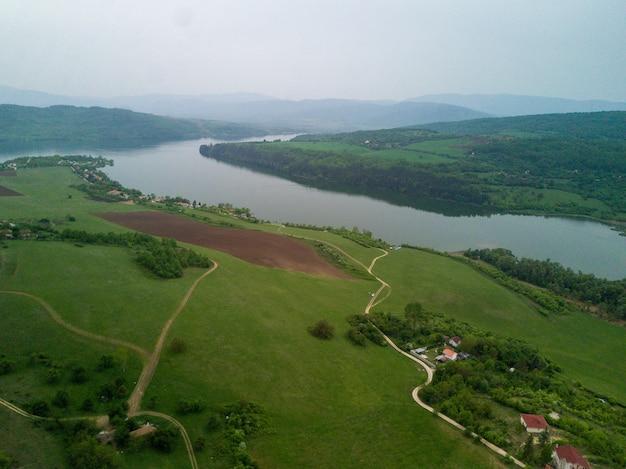 Toma aérea de los verdes paisajes, campos y un río bajo el cielo nublado en un día soleado