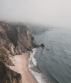 Toma aérea vertical de un acantilado junto al mar con orilla arenosa bajo un cielo brumoso
