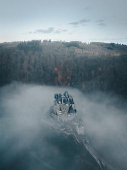 Toma aérea vertical del castillo de eltz rodeado de nubes y árboles en alemania