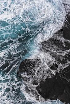 Toma aérea vertical de las olas del mar golpeando las rocas