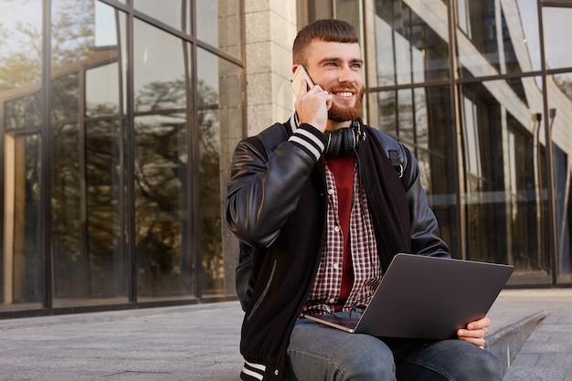 Toma al aire libre de un joven barbudo rojo fresco, sentado en la calle poniendo la computadora portátil en el regazo, tiene una conversación telefónica con un amigo, disfruta de una excelente comunicación celular y wifi gratis