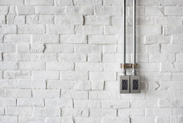 Toma de corriente en una pared de ladrillo pintada de blanco