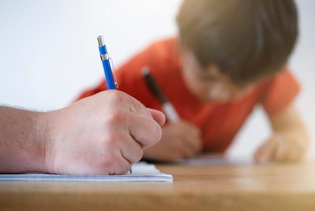Toma cortada padre ayudando a su hijo con la tarea, papá e hijo haciendo la tarea juntos, maestro enseñando al niño a escribir. mano de hombre con lápiz, concepto de educación
