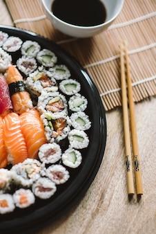 Toma de enfoque selectivo de los deliciosos rollos de sushi servidos en un plato redondo negro