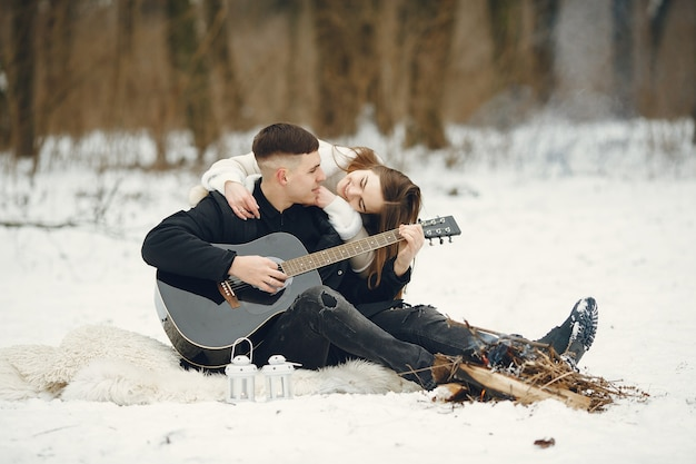 Toma de estilo de vida de pareja sentada en el bosque nevado. personas que pasan las vacaciones de invierno al aire libre. pareja con una guitarra.