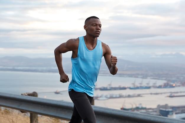 Toma exterior de un hombre afroamericano seguro de fitness que tiene un desafío de logro de objetivos para llegar a su destino sin descanso, trabaja activamente con las manos, vestido con ropa deportiva, trota sobre una hermosa vista de la naturaleza