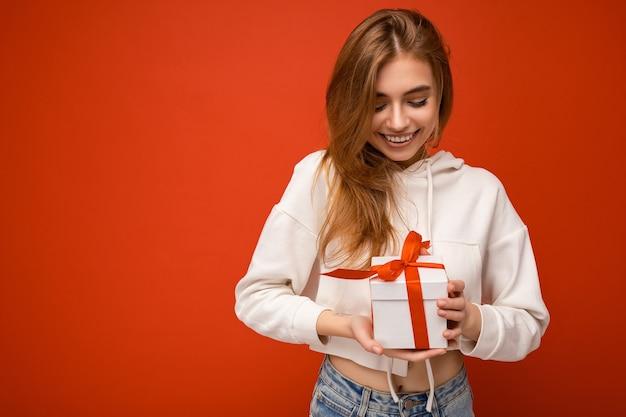 Toma de la foto de la atractiva mujer joven rubia sonriente feliz aislada sobre la pared de colores de fondo vistiendo sudadera con capucha blanca con caja de regalo blanca con cinta roja y mirando al presente. copia espacio