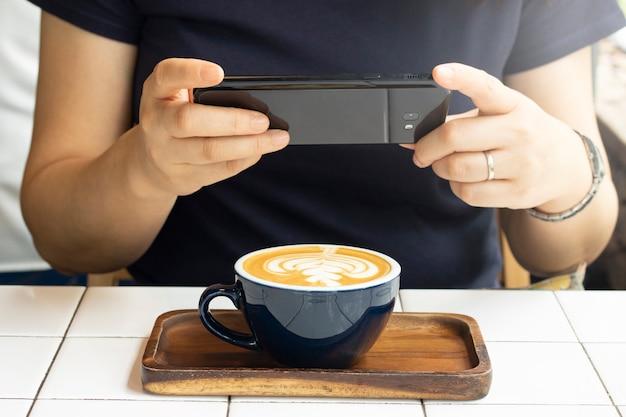 Toma una foto de café latte en una taza con teléfono móvil.