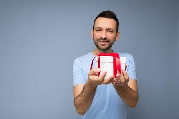 Toma de la foto de un joven guapo sin afeitar morena positivo aislado sobre fondo azul pared vistiendo camiseta azul con caja de regalo blanca con cinta roja y mirando a cámara. espacio libre