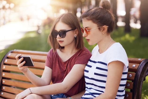 Toma horizontal de dos hermosas alumnas en ropa casual de verano