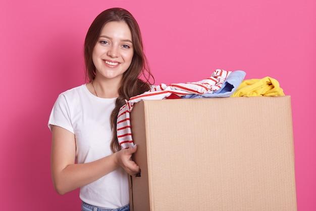 Toma horizontal de puestos femeninos sonriendo cerca de ambos con ropa reutilizable para gente pobre