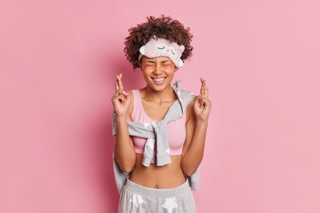 Toma interior de una adolescente feliz que se para con los dedos cruzados cree que los sueños se hacen realidad sonríe ampliamente usa ropa de dormir cómoda aplica parches de colágeno debajo de los ojos aislados sobre una pared rosa