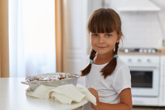 Toma interior de adorable mujer vestida con camiseta blanca con cabello oscuro y coletas posando en la cocina junto a la mesa con una deliciosa cocción, mirando sonriendo directamente a la cámara.