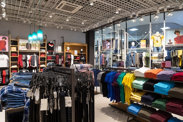 Toma interior de bastidores con camisas, camisetas y jeans