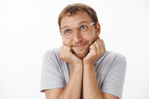 Toma interior de un chico adulto lindo y tierno con gafas y camiseta gris sonriendo con deleite, apoyando la cabeza en las palmas y mirando la esquina superior izquierda nostálgica y romántica