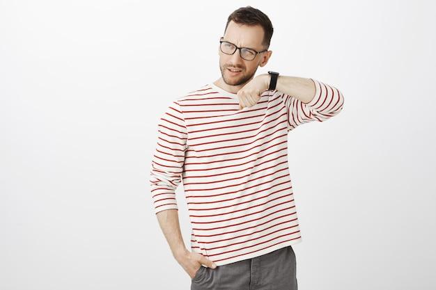 Toma interior de un chico barbudo confuso e inseguro con gafas, levantando una ceja y haciendo muecas mientras sostiene la mano cerca de la oreja y escucha el sonido del reloj digital