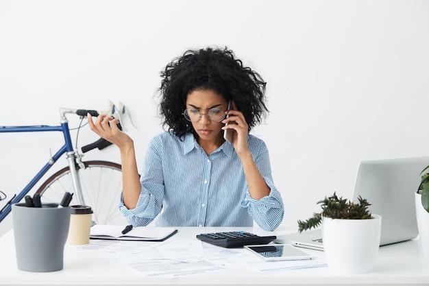 Toma interior de la empresaria afroamericana haciendo llamadas telefónicas